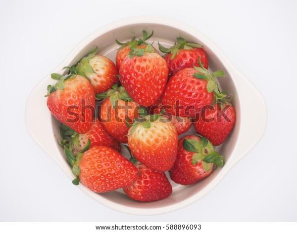 a bowl of Fresh Korean Strawberries on a white background