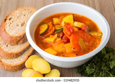 Bowl of fresh minestrone soup with bread on wood table. Traditional Italian fresh vegetable soup.
