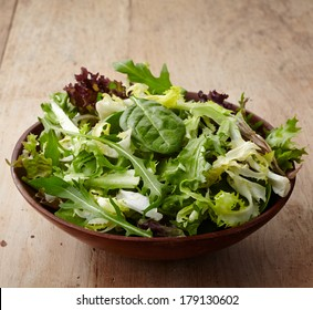 Bowl of fresh mixed salad on wooden background