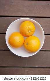 Bowl of fresh oranges on a wooden table.
