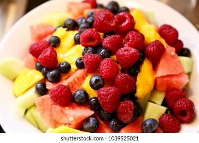 A bowl of fresh papaya, mango, watermelon, raspberries, strawberries, and blueberries.