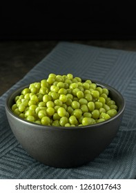 A bowl of fresh peas on a dark cloth background with copy space for your text