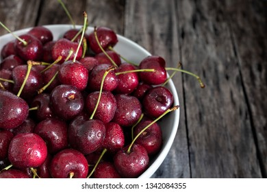 Bowl of fresh red cherries on wooden background - Image