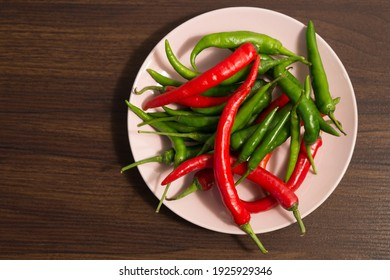 A bowl of fresh red and green chilis on a wooden table.