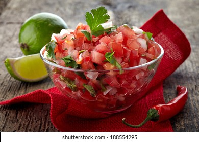 Bowl of fresh salsa dip on wooden background