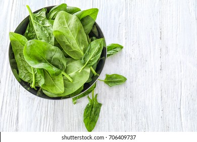 Bowl with fresh spinach leaves on table