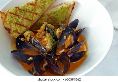 Bowl of fresh steamed mussels with garlic bread