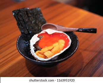 A bowl of fresh uni sashimi and kani miso topped with egg  yolk served in crab shell. Japanese traditional food.