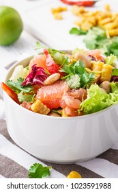 A bowl of fresh vegetarian salad with grapefruit, beans, grilled corn, lettuce and paprika on a white wooden board with napkin