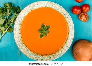 Bowl of Fresh Warming Tomato and Basil Soup Against a Blue Wooden Background