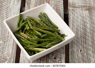 Bowl of freshly harvested Asian green beans on a weathered barn wood table cooked and ready to serve
