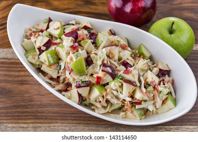 A bowl of freshly made coleslaw with red and green apples.