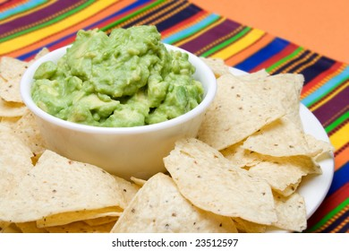 A bowl of freshly made guacamole, surrounded by fresh corn tortilla chips. Colorful background.