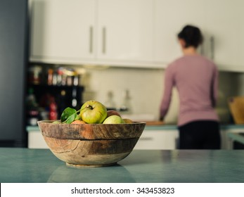 A bowl of freshly picked green apples on a table in the kitchen with a woman doing housework in the background