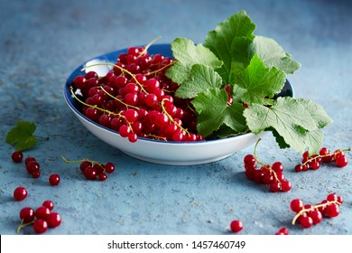 Bowl of freshly picked redcurrants and leaves on a table.