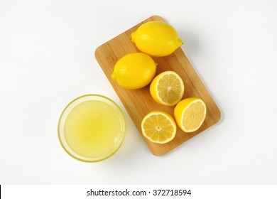 bowl of freshly squeezed lemon juice and ripe lemons on wooden cutting board