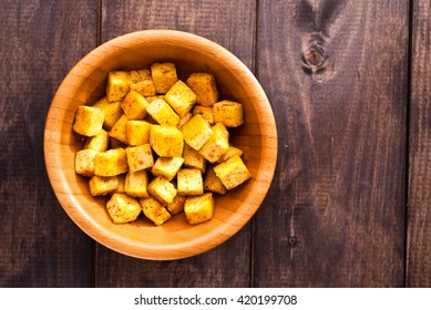 Bowl of fried tofu cubes with curry on shabby wooden background
