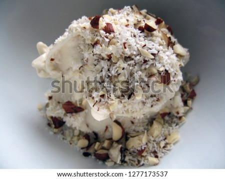 A bowl of frozen banana 'ice cream' topped with toasted coconut and almonds
