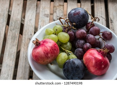 Bowl of fruit: pomegranate, grapes, plums in rural country scene-Italy, Umbria, Tuscany. Home design and healthy food choices to eat. Colorful and decorative.