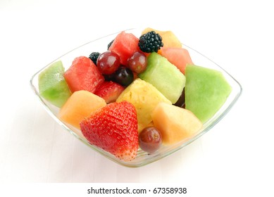 A bowl of fruit salad on a white placemat