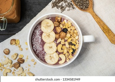 Bowl of fruit smoothie, nuts and banana, top view. Flat lay of an acai bowl with cereals, cashews and hazelnuts on vintage rustic table