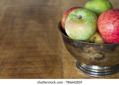 A bowl of fruit in a tarnished pewter bowl on a wooden table