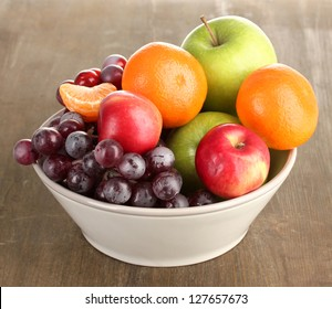 Bowl with fruits, on wooden table
