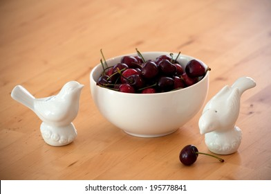 Bowl full of cherries with bird figurines