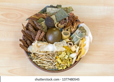 Bowl full of dried Chinese mixed herbs to make cooling drinks in traditional Chinese medicine on wooden background
