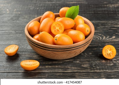 Bowl full of fresh fruit kumquat on the wooden background