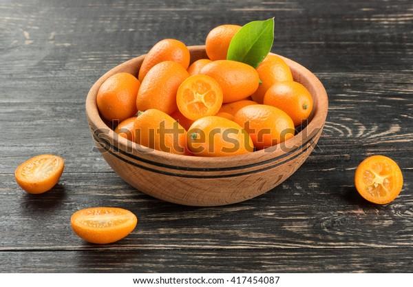 Bowl full of fresh fruit kumquat on the wooden background