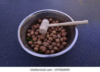 An bowl full of nuts with a mallet.