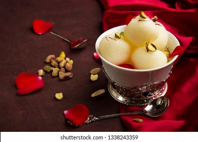 Bowl full with Rasgulla and pistachios, a food table top, Pune, India.