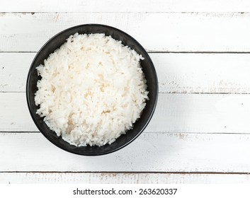 bowl full of rice on white wood