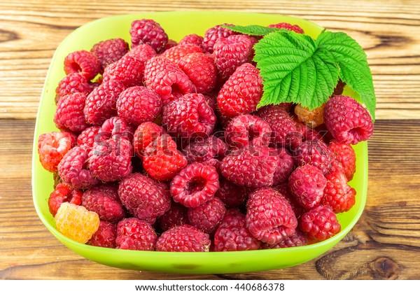 Bowl full of ripe raspberries on rustic wooden table
