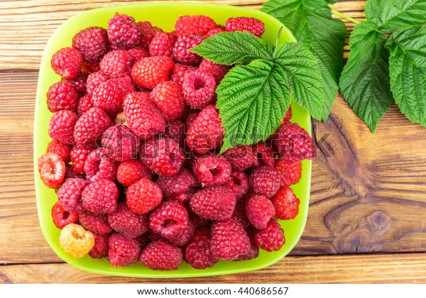 Bowl full of ripe raspberries on rustic wooden table, top view