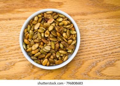 Bowl Full of Roasted Pumpkin Seeds on an oak table