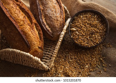 Bowl full of rye on sackcloth with loaf of bread. Healthy organic ingridients for diet.