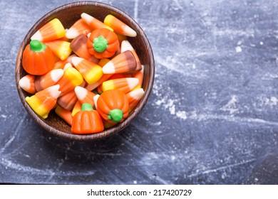 A bowl full of seasonal Halloween candy corn, a traditional fall treat.