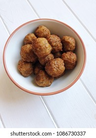 bowl full of small fried meatballs on white wooden table, finger food snack