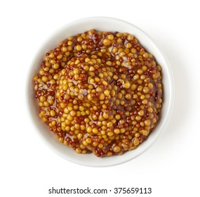 Bowl of full wholegrain mustard on white background, top view