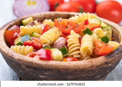 Bowl of fusili pasta salad with fresh vegetables