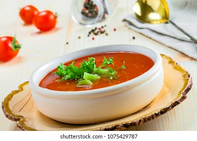Bowl of gazpacho, bread and vegetables on a table. Tasty Spanish vegan soup. Close-up shot.