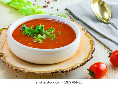 Bowl of gazpacho, bread and vegetables on a table. Tasty Spanish vegan soup.