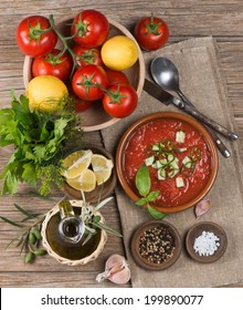Bowl of gazpacho with  tomato and other vegetables on wooden table.  Top view.