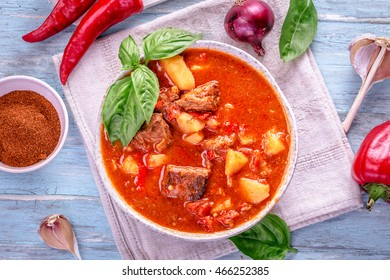 Bowl of goulash on light cyan background. Traditional hungarian meal - beef stew. Toned.