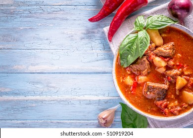 Bowl of goulash on light cyan background with copy space. Traditional hungarian meal - beef stew.