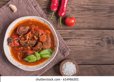 Bowl of goulash on rustic wooden background. Traditional hungarian meal, beef stew. Toned. Copy space