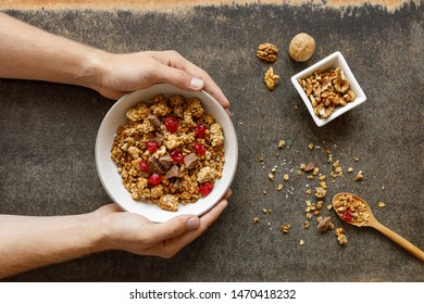 Bowl of granola with dried berries, walnuts and chocolate. Top view. Male hands holding the bowl