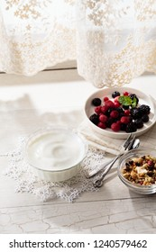 Bowl of  granola with homemade yogurt and fresh berries on wooden background